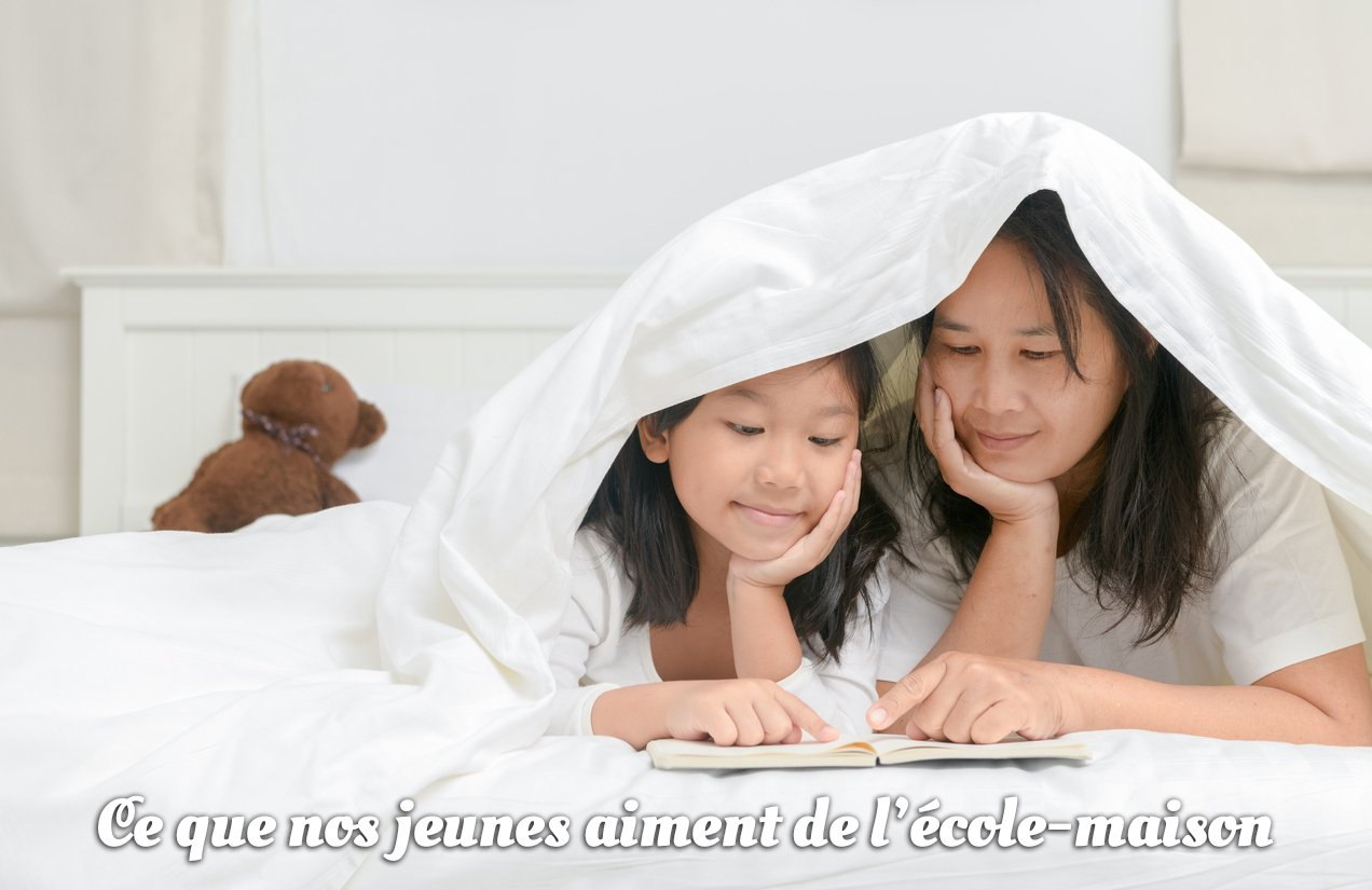mother and daughter reading together under bed covers